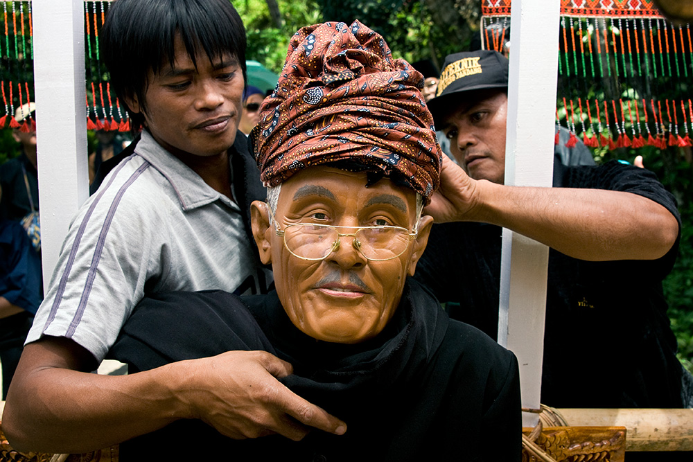 The statue portraying a deceased man is prepared for the procession. The statue as well as the coffin will be carried during the walk in the village and return to the ceremony place at the end.