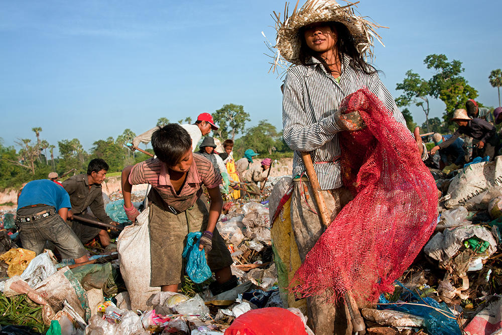 A girl together with other garbage dump residents browse recently dumped waste looking for recyclable material or any other useful objects.