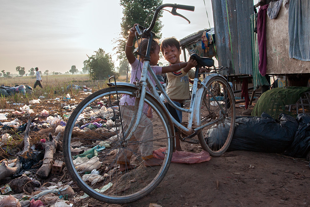 Two children in front of one of the houses on a garbage dump in Siem Reap.
