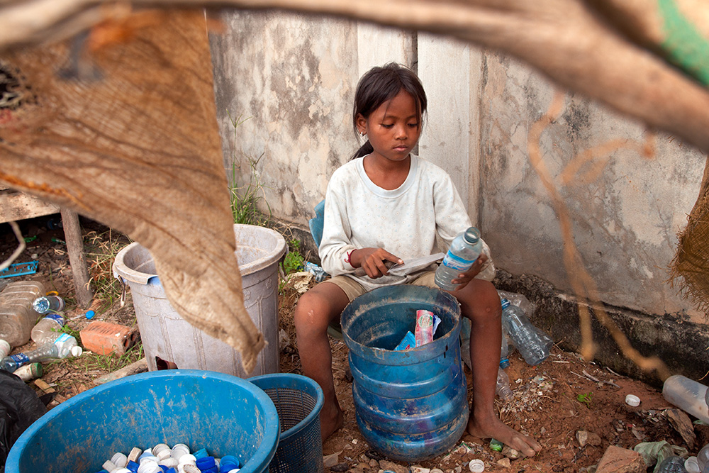 A young girl works in a storage warehouse in Siem Reap. She cleans the bottles with a knife and sort them among the containers.